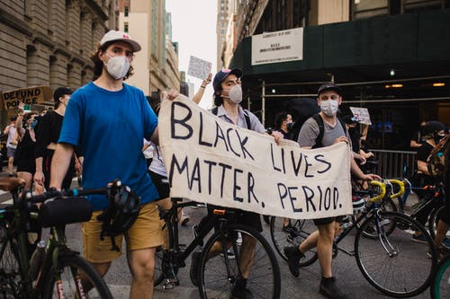 "Cyclists holding up sign, ""Black Lives Matter. Period."" Life Matters"