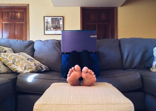 Barefoot person with laptop on couch. Image by Pixabay at www.pexels.com.