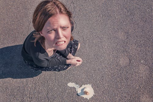 Woman drops her ice cream cone and looks upset. Gratistography.