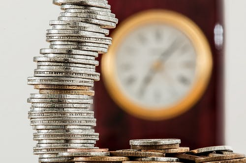 stack of coins with clock in the background; image by Pexels