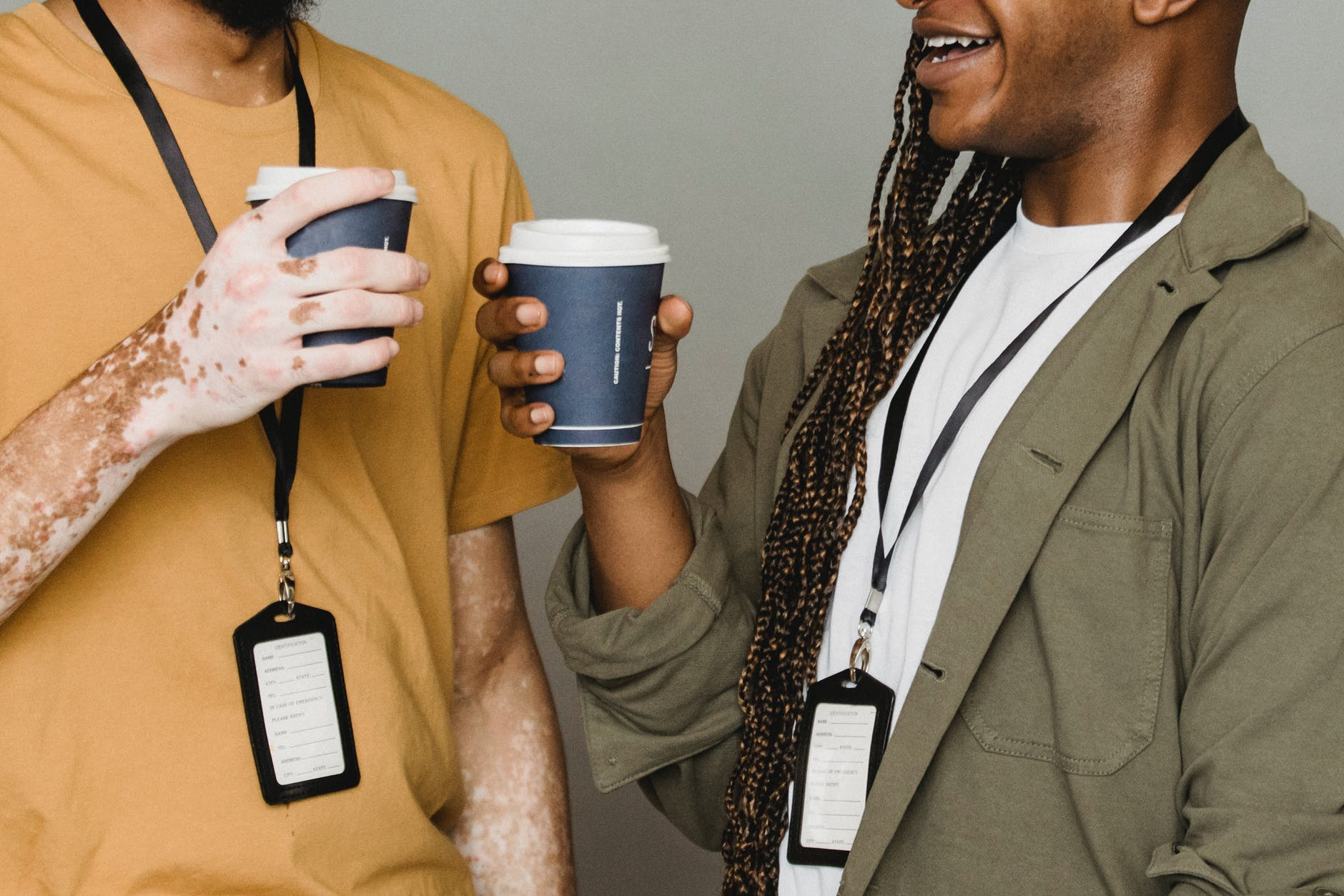 two men with lanyards and holding coffee having conversation, image by Armin Rimoldi on Pexels.com