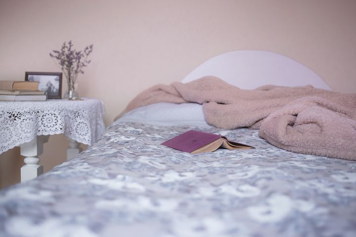 Bed with open book on top. Image by Pixabay